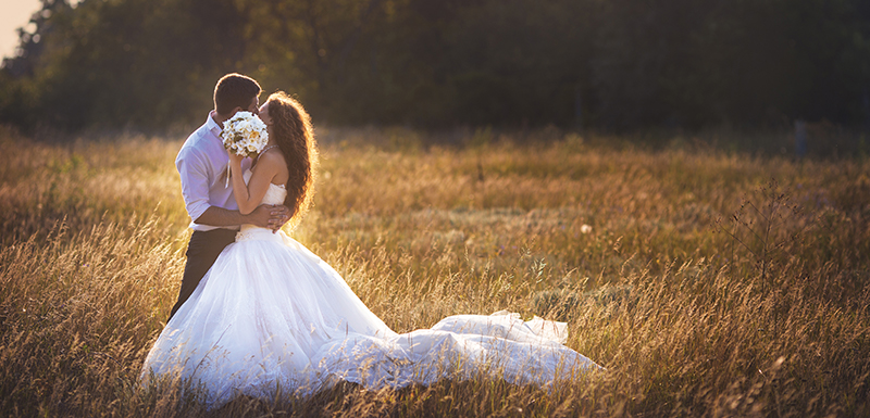 Bride and groom kissing at Hunter Valley Wedding Venues with sun setting in summer and friends and family staying at Oaks Cypress Lakes Resort nearby