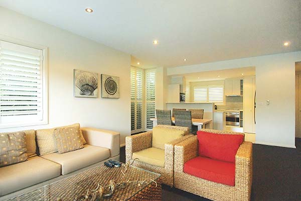 lounge area with comfortable couches in 1 bedroom hotel apartment nelson bay new south wales nsw