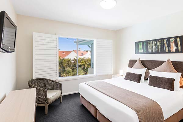 master bedroom at oaks pacific blue resort with flat screen television and views of swimming pool outside