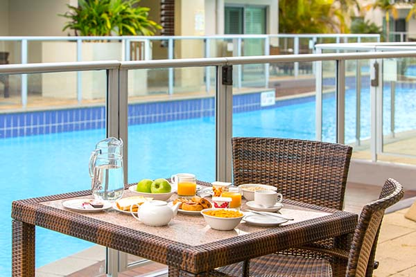 breakfast on table on balcony at oaks pacific blue resort hotel in port stephens with swimming pool in background