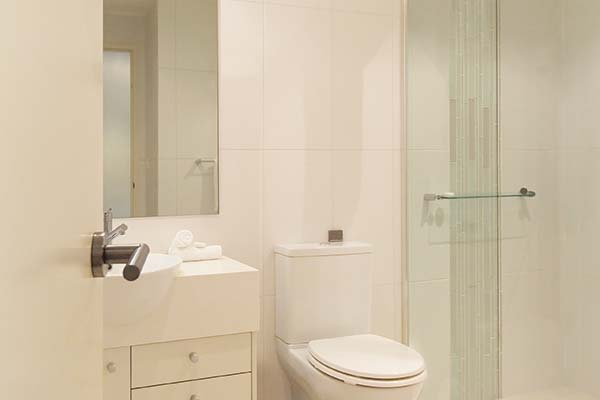 studio apartment bathroom with shower and toilet at oaks pacific blue resort in port stephens