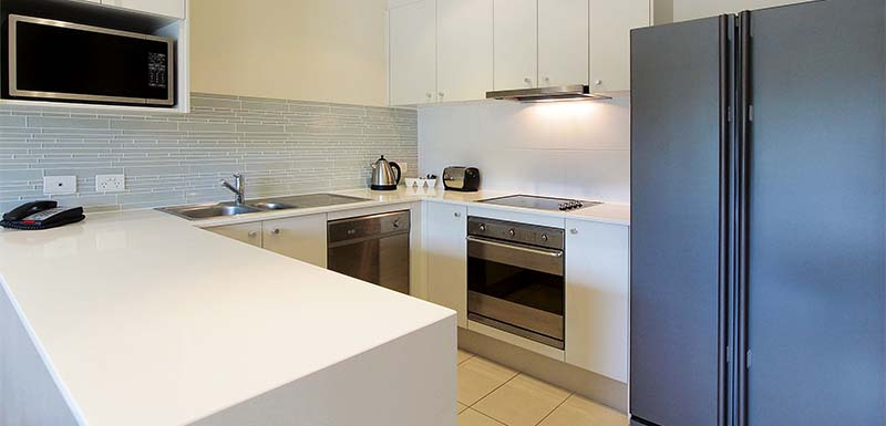 spacious kitchen area with big fridge oven stove top and microwave