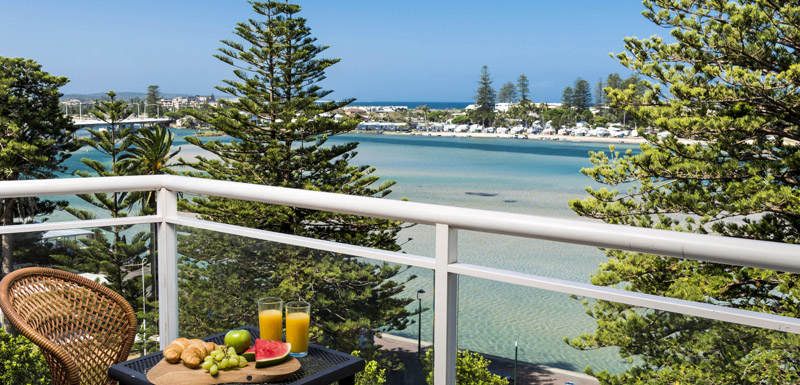 balcony with breakfast on table and view of ocean in background during summer