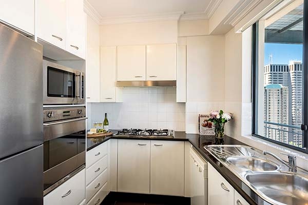 3 bedroom apartment kitchen with oven, microwave, cook top and full-size fridge in Sydney city centre