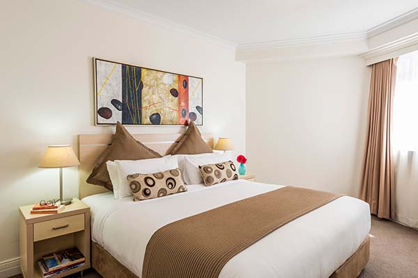 master bedroom with large, comfortable bed and cupboards for storage during holiday stay