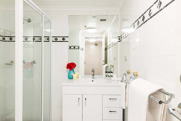 en suite bathroom with fresh towels, big shower and vanity cabinet for hotel visitors in Sydney CBD
