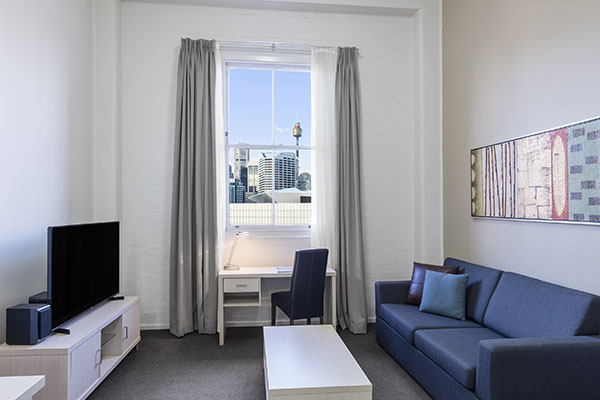 Large Lounge Room At Oaks Goldsbrough Apartments With Views Of Darling  Harbour And Work Space Including