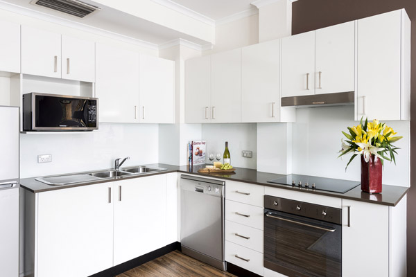 spacious kitchen area with oven, microwave and washing machine for hotel guests