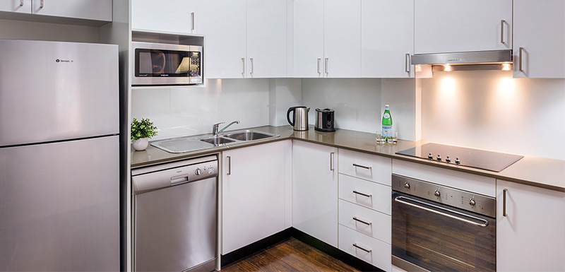 fully-equipped kitchen with stove, oven, dishwasher, microwave and fridge at oaks goldsbrough darling harbour sydney hotel