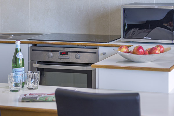 oven, stove top, microwave and dining table in the kitchen of oaks hyde park sydney hotel