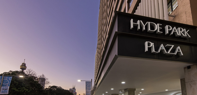 Large sign at entrance to Hyde Park hotel Sydney city at sunset with car parking outside