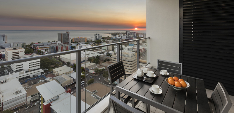 Darwin hotel balcony with fresh breakfast on table and views of Darwin Harbour in the morning
