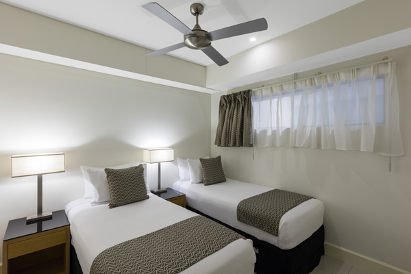two single beds with ceiling fan and air conditioning in Darwin hotel 2 bedroom apartment