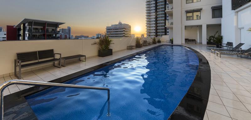 swimming pool with sun loungers at sunset at Oaks Elan Darwin hotel Northern Territory, Australia