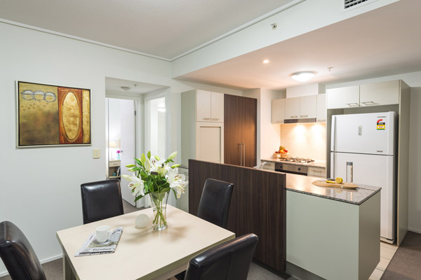 modern kitchen with full-size fridge, oven and microwave leading out to large living room space at Oaks Aurora hotel on Queen Street
