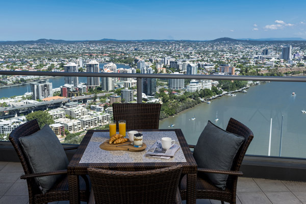 table with chairs and lunch on balcony at 1 bedroom hotel apartment at Oaks Aurora with views of Brisbane River in daytime