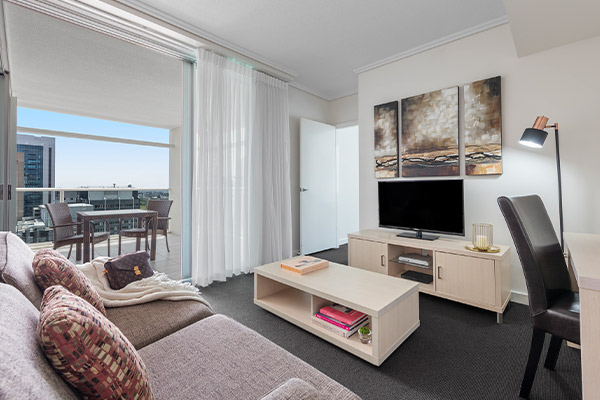 spacious living room connected to a balcony at Oaks Brisbane Casino Tower Suites 1 Bedroom Apartment