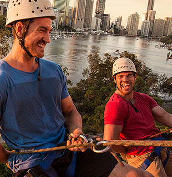 two men climbing kangaroo point cliffs in Brisbane with city and Brisbane River in background