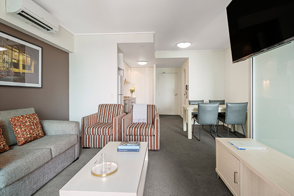 1 bedroom executive apartment living room with balcony and views of Story Bridge and Brisbane River