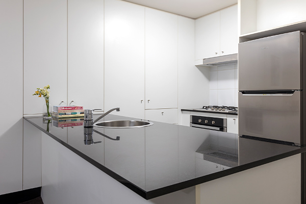 modern kitchen with fridge, oven and large cupboards in 2 bedroom apartment in Brisbane city