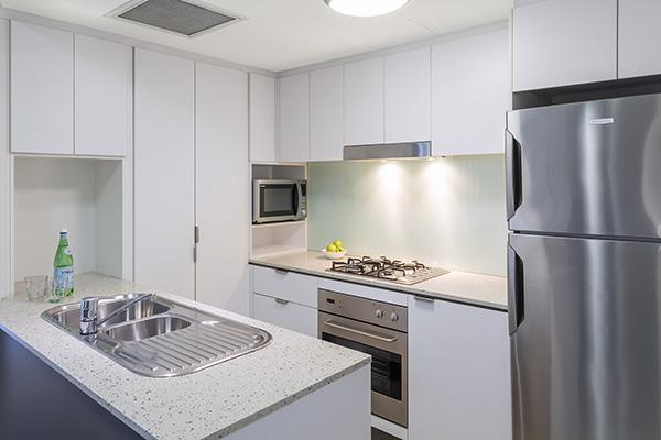 Kitchen with full size fridge inside 1 bedroom hotel apartment Brisbane CBD