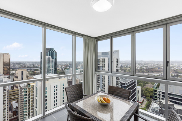 1 bedroom executive apartment balcony with table, chairs and view of Brisbane city at Oaks Festival Towers hotel