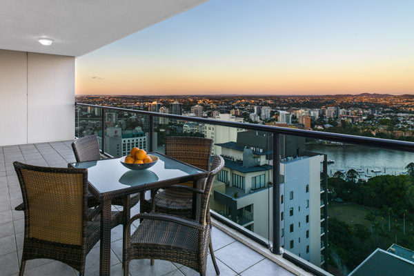 large balcony area with table at Hotel in Brisbane CBD with panoramic view of Brisbane River at sunset at iStay River City hotel