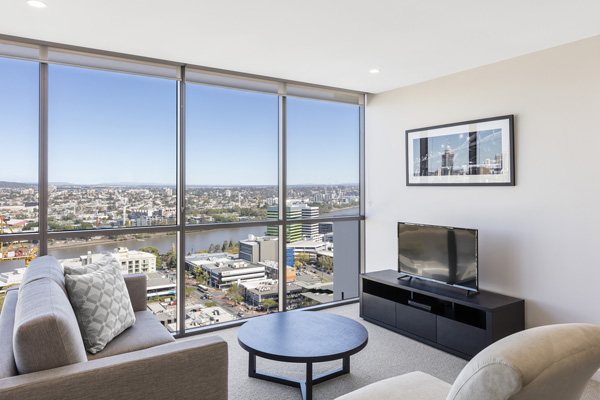 living room with large windows, views of Brisbane River and foxtel on television in 2 bedroom apartment at The Milton Brisbane hotel