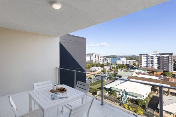 hotel balcony with furniture and views of Brisbane walking distance to The Gabba stadium