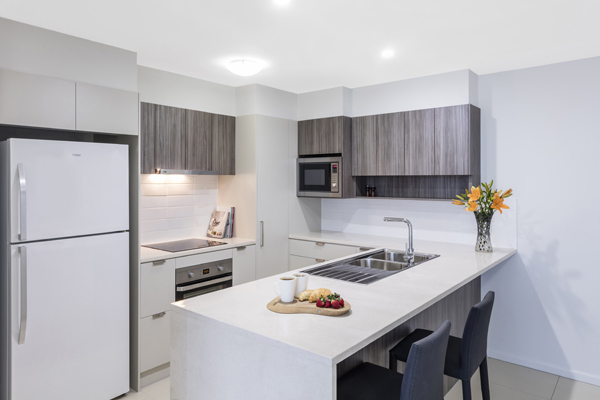 1 bedroom apartment with kitchen that has large fridge and microwave at Oaks Woolloongabba hotel