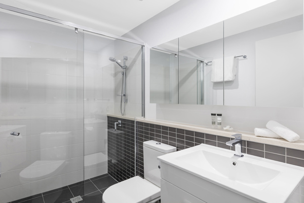 big en suite bathroom with adjustable shower head and toilet in 2 bedroom apartment at Oaks Woolloongabba hotel