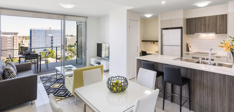 Oaks Woolloongabba hotel 1 bedroom apartment living room area with air conditioner, flat screen TV and balcony