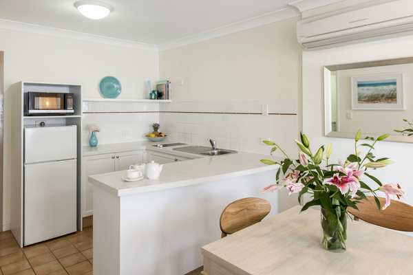 kitchen area with dining room table, fridge and microwave at Oaks Calypso Plaza hotel resort in Coolangatta near beach