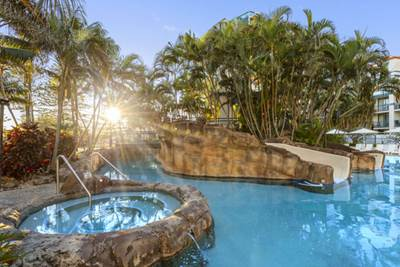 large swimming pool and jacuzzi at Oaks Calypso Plaza hotel resort in Coolangatta on Gold Coast at sunset