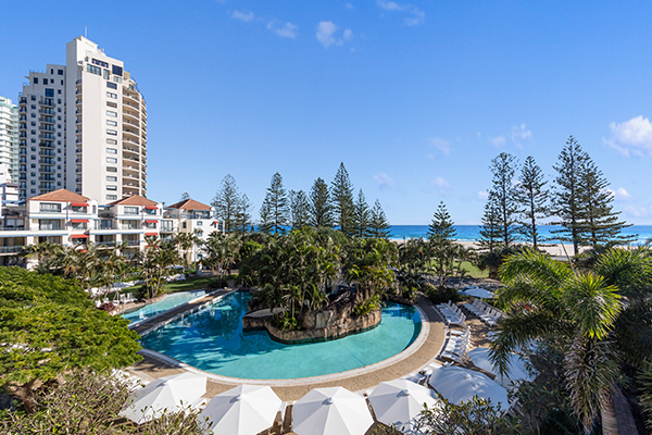big resort swimming pool near beach in Coolangatta with blue skies and ocean in background, Gold Coast, Australia