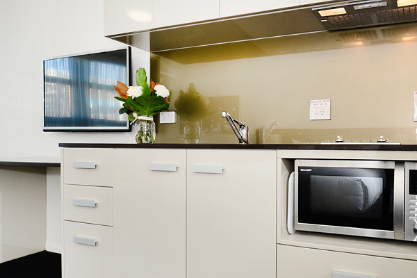 modern kitchen in one bedroom apartment with microwave and television at Oaks Grand Gladstone hotel