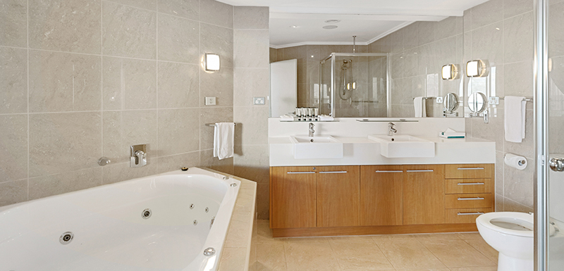 Ensuite bathroom with hot tub bath in 2 bedroom hotel apartment at Oaks Hervey Bay resort