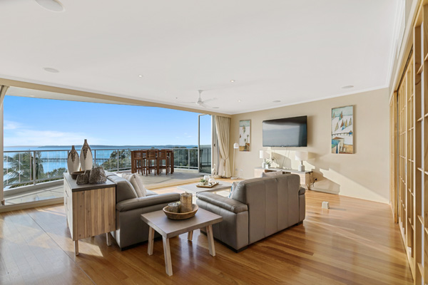 Spacious lounge with couches and TV facing big balcony in 2 Bedroom Penthouse, Hervey Bay