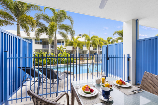 courtyard of 1 bedroom apartment leading out to large swimming pool at Oaks Lagoons hotel in Port Douglas