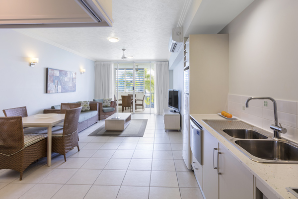 open plan living room leading out to balcony of 2 bedroom apartment at Oaks Lagoons hotel in Port Douglas