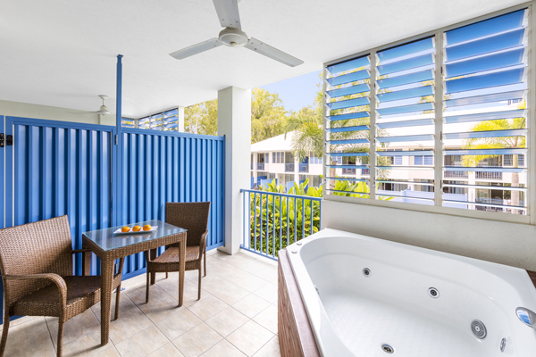 spa bath on balcony with table and chairs at 2 bedroom apartment at Oaks Lagoons resort in Port Douglas