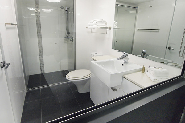 Studio apartment en suite bathroom with toilet, shower, clean towels and mirror at Oaks Metropole Hotel in South Townsville