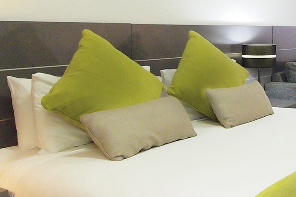 Green pillows on clean bed sheets on double bed in studio room at Oaks Metropole Hotel in Townsville