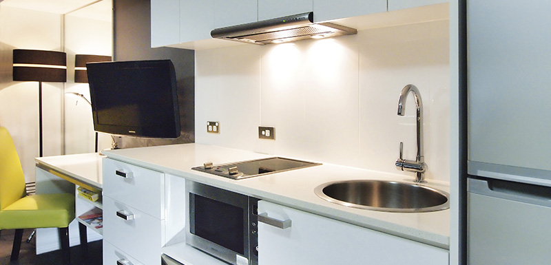 kitchen with full-size fridge, microwave and TV in air conditioned Studio Apartment at Oaks Townsville Metropole Hotel in Townsville