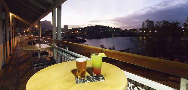 glass of beer and cocktail on table with views of Townsville at sunset at Metropole Hotel restaurant