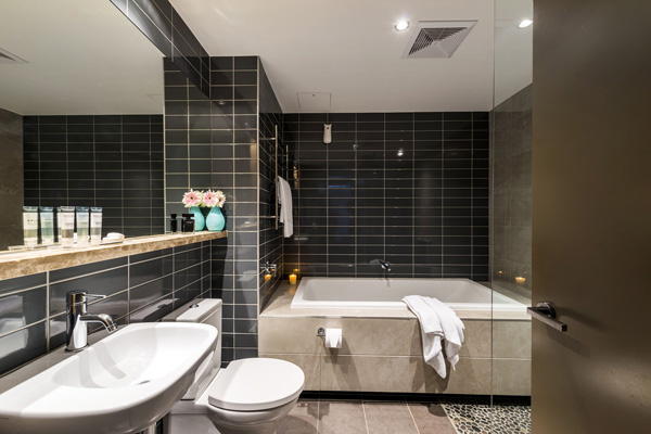 en suite bathroom with bathtub, toilet and clean towels at Mon Komo Hotel in Redcliffe, Queensland