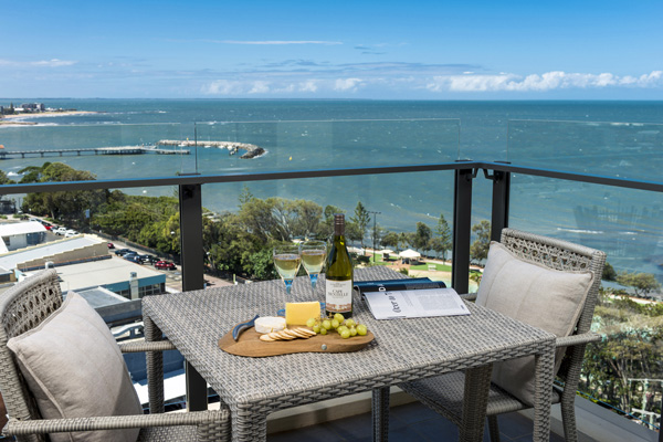 Redcliffe accommodation with private balcony of 2 bedroom apartment with table and chairs and view of ocean at Oaks Mon Komo Hotel in Redcliffe
