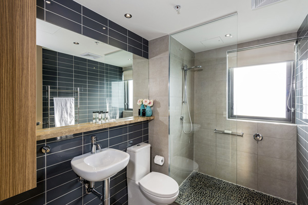 large shower and toilet in en suite bathroom of 3 bedroom apartment at Mon Komo Hotel in Redcliffe