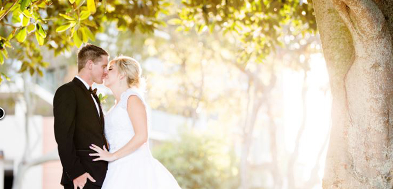 happy couple kissing under tree at Redcliffe wedding venues in Moreton Bay, Queensland, Australia