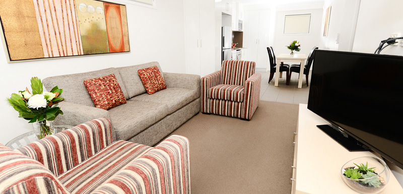 spacious living room of 2 bedroom hotel apartment with couches, dining table and TV for guests